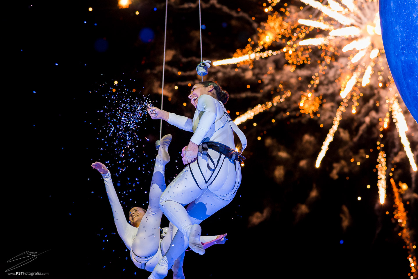 Bailarinas aéreas sonriendo con fuegos artificiales al fondo