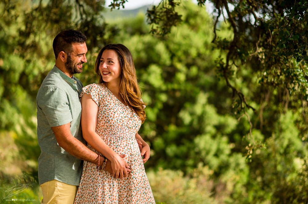 Pareja de enamorados se miran y sonríen, sesión de embarazo en Alcoy. PSTFotografía