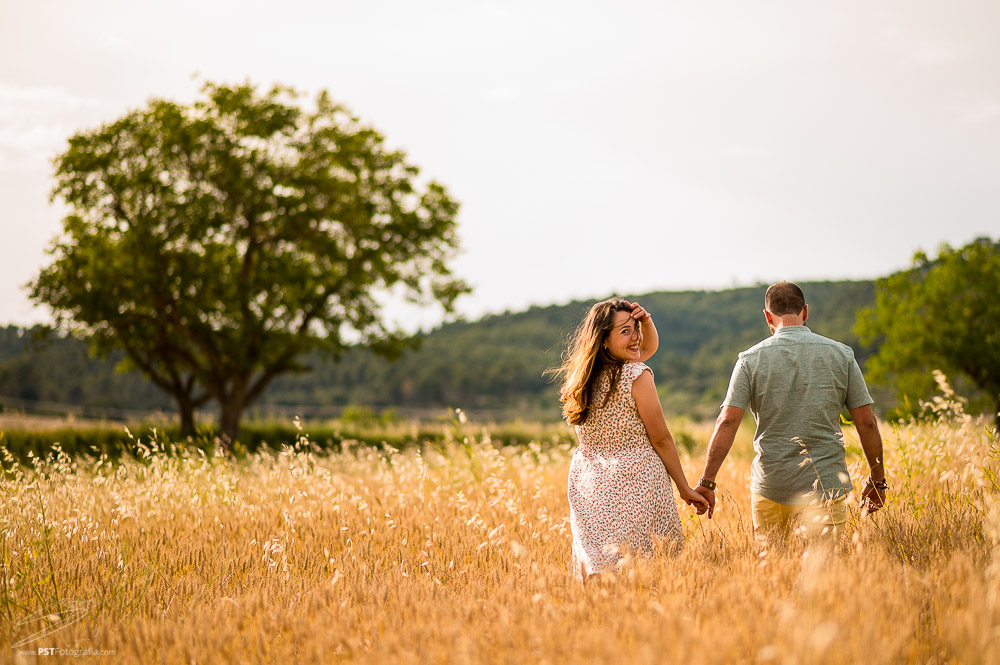 Pareja paseando por campos de trigo mientras ella mira hacia la cámara. Embarazo en Alcoy